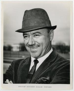 Black and white photo of a man in a hat, wearing a corduroy jacket and a tie. He is seen from his shoulders up.