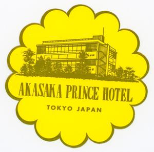 A circular tag, a picture of a white hotel building, a blue sky at the top. The tag is attached to a light blue string.
