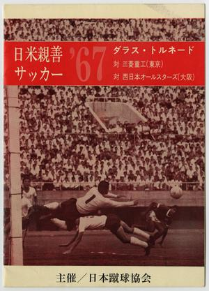 A book cover with a red tinted photograph of a soccer match in action, the crowd in the stands seen behind them. A red block is at the top, the number 67 on it.