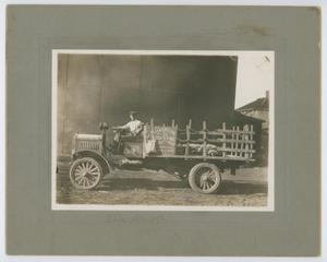 Black and white photograph of a man in a truck. The left side of the truck is seen, a sign on the side of it.