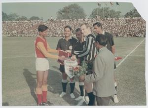 Photo of a young man in a red and white soccer uniform, flags being handed to him by 5 other men. One of them has a black and white shirt. Another man has a suit and holds flowers.