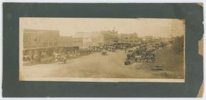 Old photograph in the shape of a long rectangle. Buildings align the left side of the photo, with the street on the right and several wagons with horses can be seen. The photo lays on a black page with worn edges.