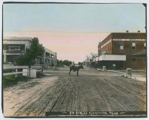 Picture in color. The sky is light blue and pink. On the left side of the photo is an old white building. The right side of the photo is brown. The words John J. William are on it. In the middle of the picture, a man on a horse is in the middle of a gravel road.