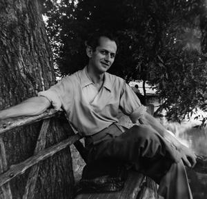 A young man sits on a wooden bench by a tree trunk