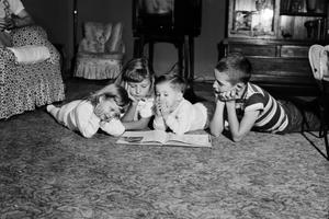 Four young children laying on the carpet. The two children on the left are girls, the two on the right are boys. There is a book open in front of them.