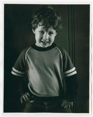 A young boy poses with his hands on his hips, seen from the waist up.