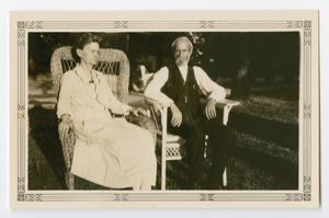 An old woman sits on a chair, a man on the right of her also sitting on a similar chair. The chairs are on a lawn.