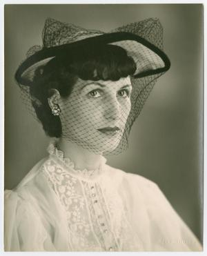 Photo of a woman wearing a white ruffled shirt with a white and black hat, and a mesh veil over her face. She looks to the right with a stoic expression.