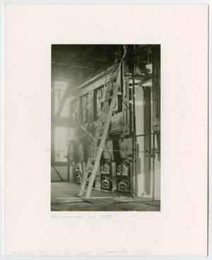 Black and white photo of an open space with a ladder leaned against a wall.