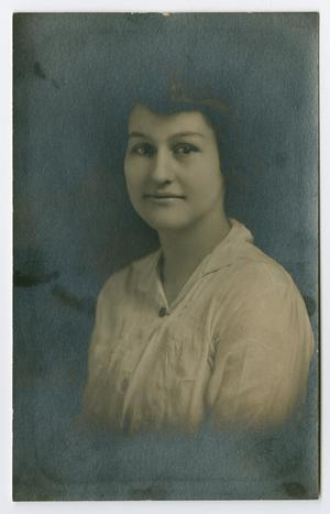 Old photograph of a young woman with a white shirt and short hair, slightly faded by a black background.