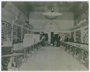View of a long room with shelves on th right and left side and tables. There are people standing at the end of the room.