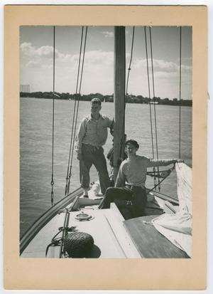 Black and white photo of two men on the deck of a ship, the water is seen behind them.