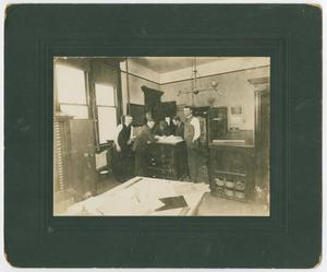 Black and white photo of five different man standing around a dresser, in a room with a big table. The photo is on a black page.
