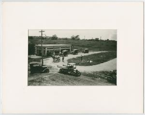 Foto en blanco y negro de varios autopista viejos junto a un camino de entrada, algunos caballos están en ella. Hay un pequeño edificio.
