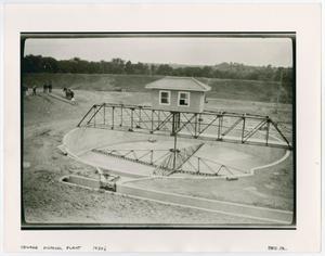 Foto en blanco y negro de un edificio en forma de torre, con una pasarela sobre él. Hay túneles en la tierra, y está aislado por una colina. Se ven personas en el fondo junto a ella.