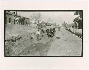 Foto en blanco y negro de hombres y mulas de pie sobre un terreno de tierra.