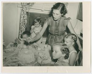 Black and white photo of a woman standing at a table, four kids sitting around her. On the table is a cake.