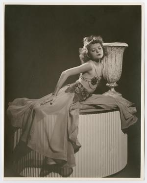 Black and white photo of a young girl in a metal bra and long skirt, posing on top of a stand.