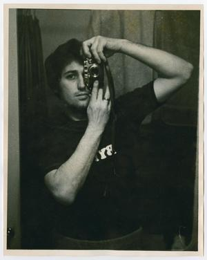 A man holds up a camera, taking a picture of himself in the mirror with it.