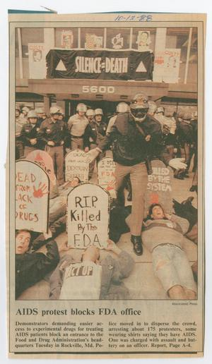 Newspaper clipping showing a page filled with a picture of a protest in front of a building. A sign towards the back says Silence-Death. At the front are people laying on the ground, holding tombstone shaped signs that say things like RIP Killed By The FDA. Behind them are police officers standing up.