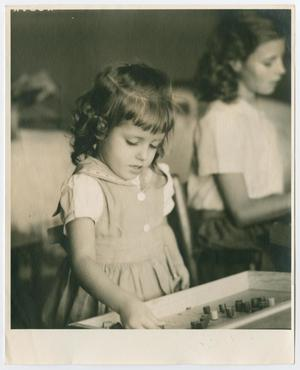 A young girl in a dress, playing with blocks on a table.
