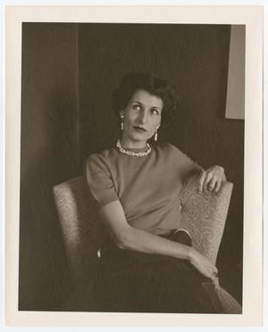 Foto antigua de una mujer con pendientes colgantes y un collar corto. Ella está sentada en una silla estampada.
