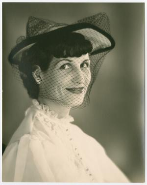 Photo of a woman wearing a white ruffled shirt with a white and black hat, and a mesh veil over her face. She smiles at the camera.