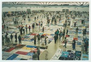 A room of people are seen looking at quilts displayed on the ground in a big room.