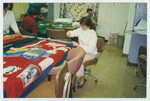 A woman is seen sitting at a chair by quilt fabric laying at a table. Other people are seen behind her.