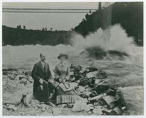 A woman in a big dress sits next to a man in a suit to her left. They sit on rocks, the water by them splashing up.