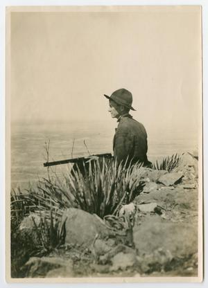 Photo of a man stting on rocks by a body of water. He is wearing a uniform, holding a long rifle.