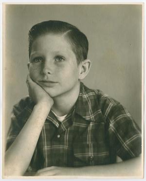 Black and white photo of a young boy in a plaid shirt, his hair slicked back and his chin in his hand.