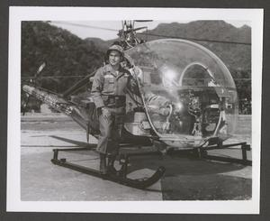 Black and white photo of a man with glasses in an army uniform standing outside on the edge of a helicopter that is covered by a clear shield.
