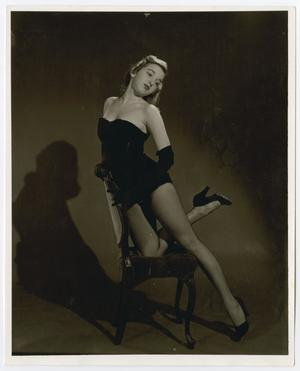 Female ballet dancer in a small black outfit and fishnet stockings. She is posing on a chair.