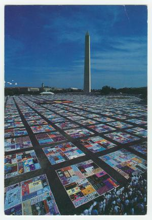 A bunch of quilts are lying across the ground over a giant expanse, a tall thin tower can be seen in the distance.