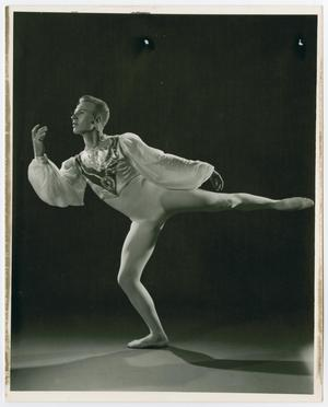 A male ballet dancer wearing an all white outfit. He is standing, posing on his right leg.