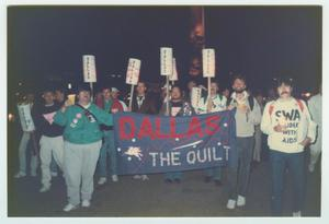 People walking together, some holding signs that say Dallas. Some hold a blue banner that says Dallas The Quilt.