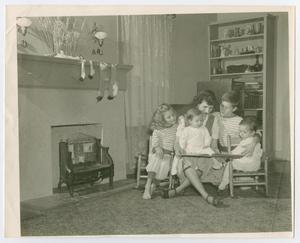 Black and white photo of a woman sitting on a couch, four children sitting around her. There is a fireplace to their left, and a bookcase behind them.