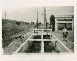 A construction project is seen deep in the ground, a hole in th shape of a rectangle. There are several cars in th background, a man standing on the right side of it.
