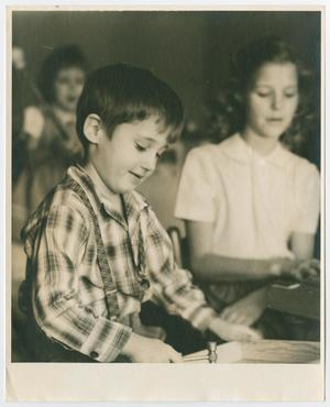 Black and white photo of a young boy at a desk, a young girl in the background by him.