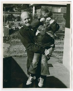 An older man stands outside, while holding up a young boy. There is a wire fence behind them.
