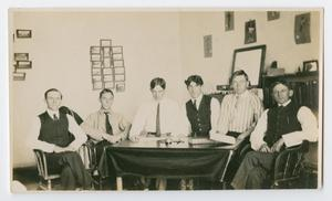 Six different men sit by each other at a table. Behind them are some papers hung on the wall.