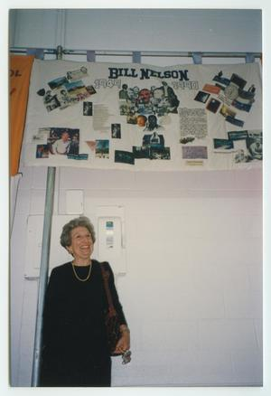 An older woman in a black dress stands under a quilt panel displayed hanging up. The panel is titled Bill Nelson.