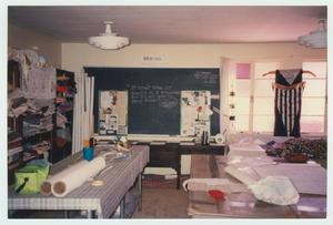 A room with fabric set up on some tables is seen. On the left side of the photo are shelves filled with fabric. In the back of the room is a chalkboard.