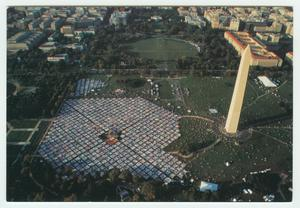 The big quilt memorial can be see from an aerial view, a tall thin building next to it on the right, and other buildings and trees seen in the distance.