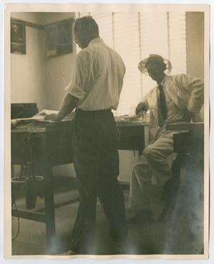 A man stands at a table, another man sitting at a chair looking towards him (wearing all white).
