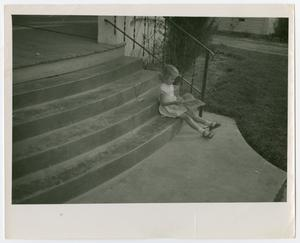 A little girl sitting on a staircase outside, reading a paper.