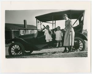 A woman stands next to an old vehicle, two children standing on the steps of it. They are by a house behind the car.