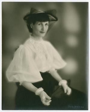 Foto de una mujer con camisa blanca y sombrero blanco y negro, malla sobre su cara. También lleva una falda negra y guantes blancos.