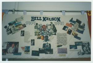 A quilt panel on display hanging up, the words Bill Nelson at the top followed by different pictures on it.